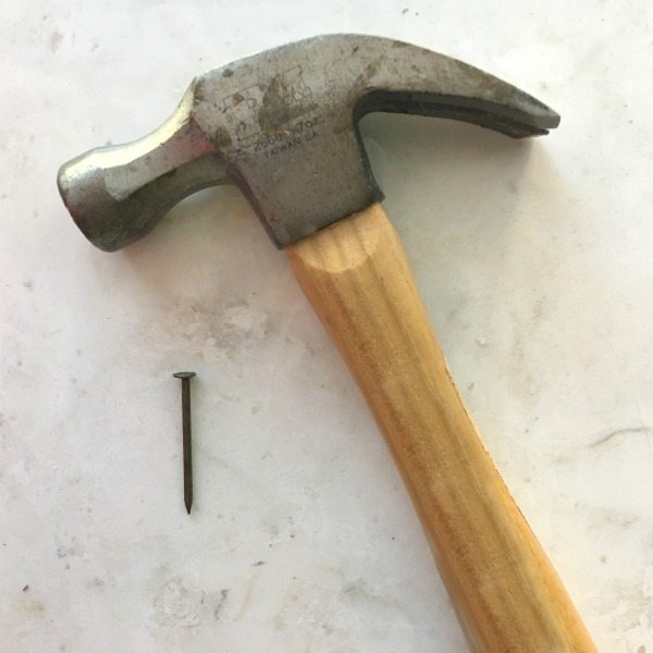 Hammer and nail to hang a boxwood wreath for Christmas