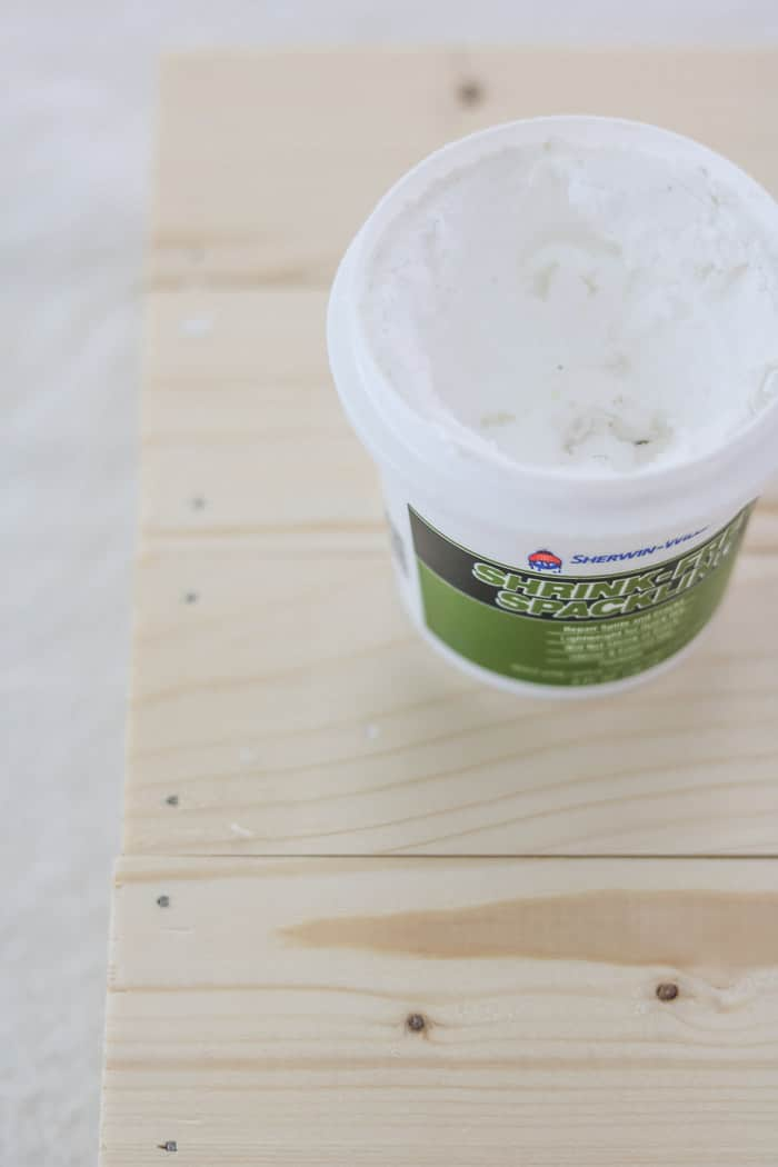 An open container of spackling on a board