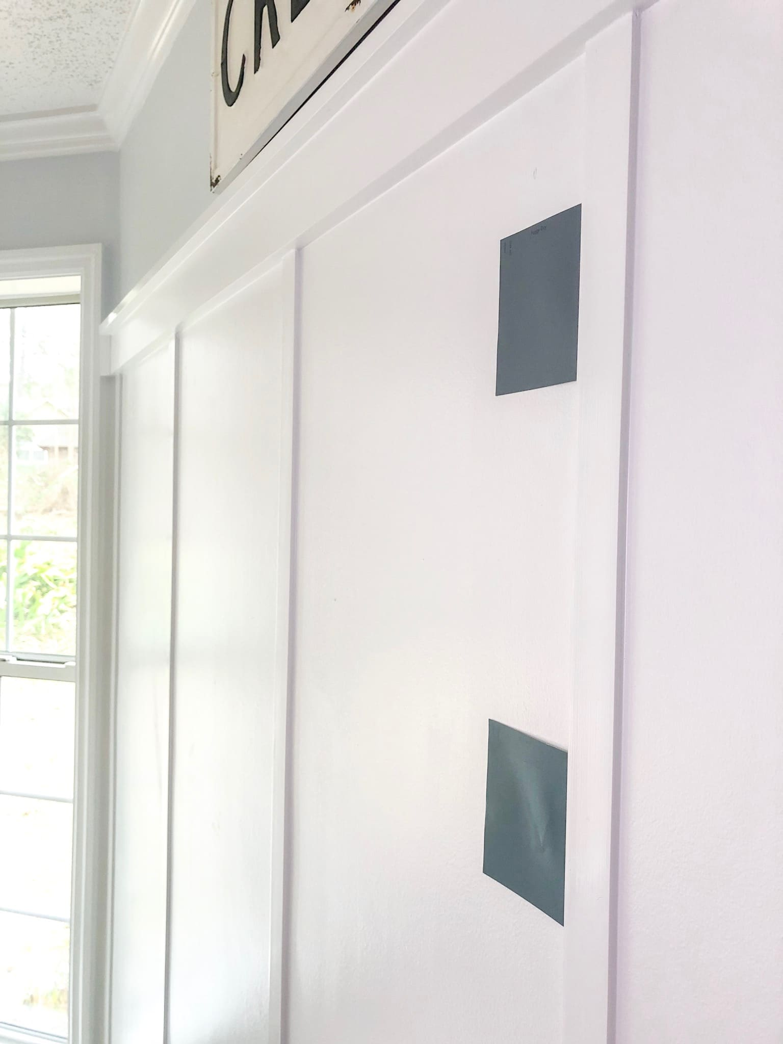 samples of fixer upper paint colors mounted to a board and batten wall