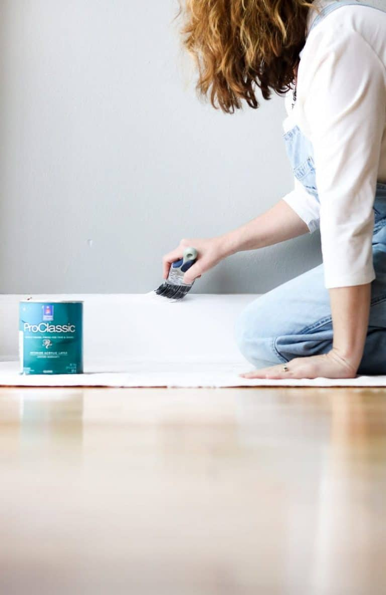 best diy painting tools showing me painting the floor boards on a dropcloth