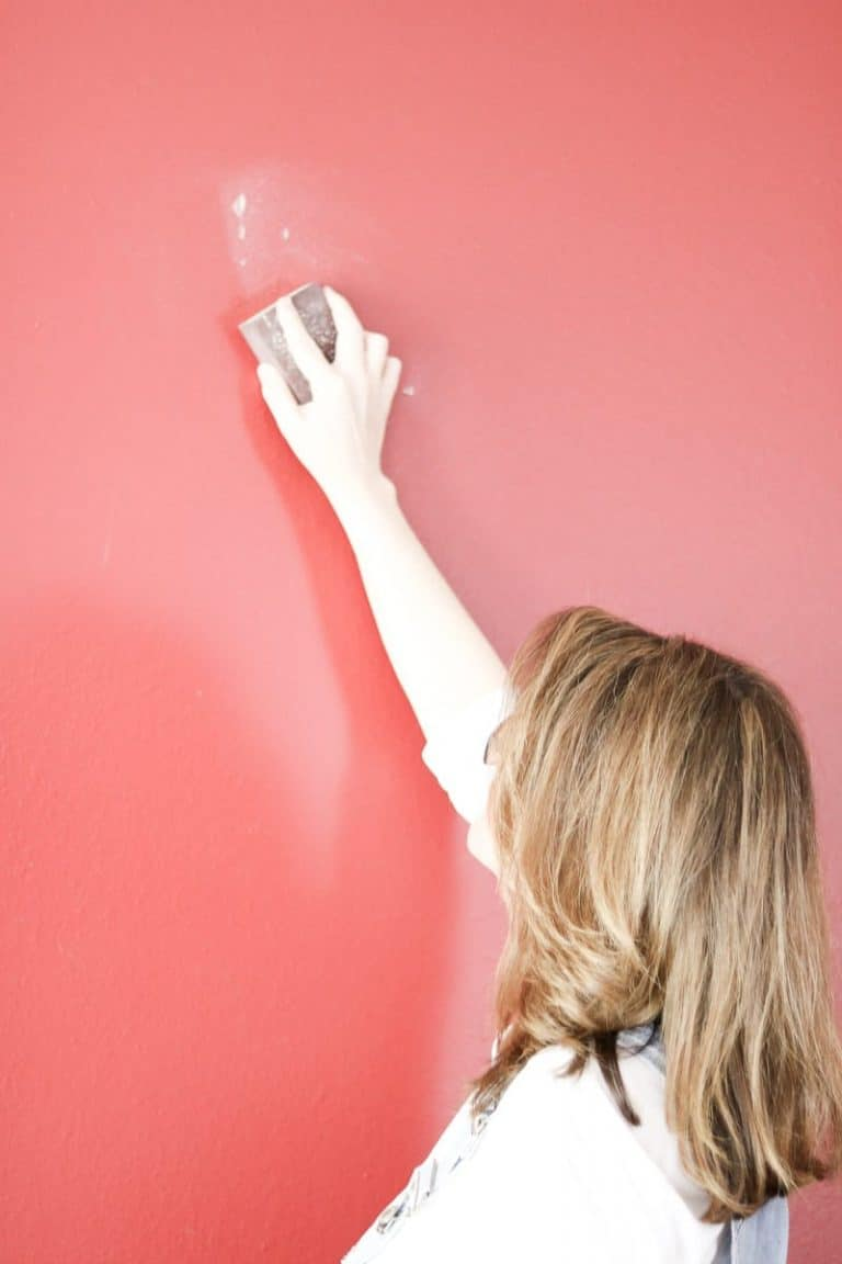 Sanding a wall after spackling has had a chance to dry, before painting