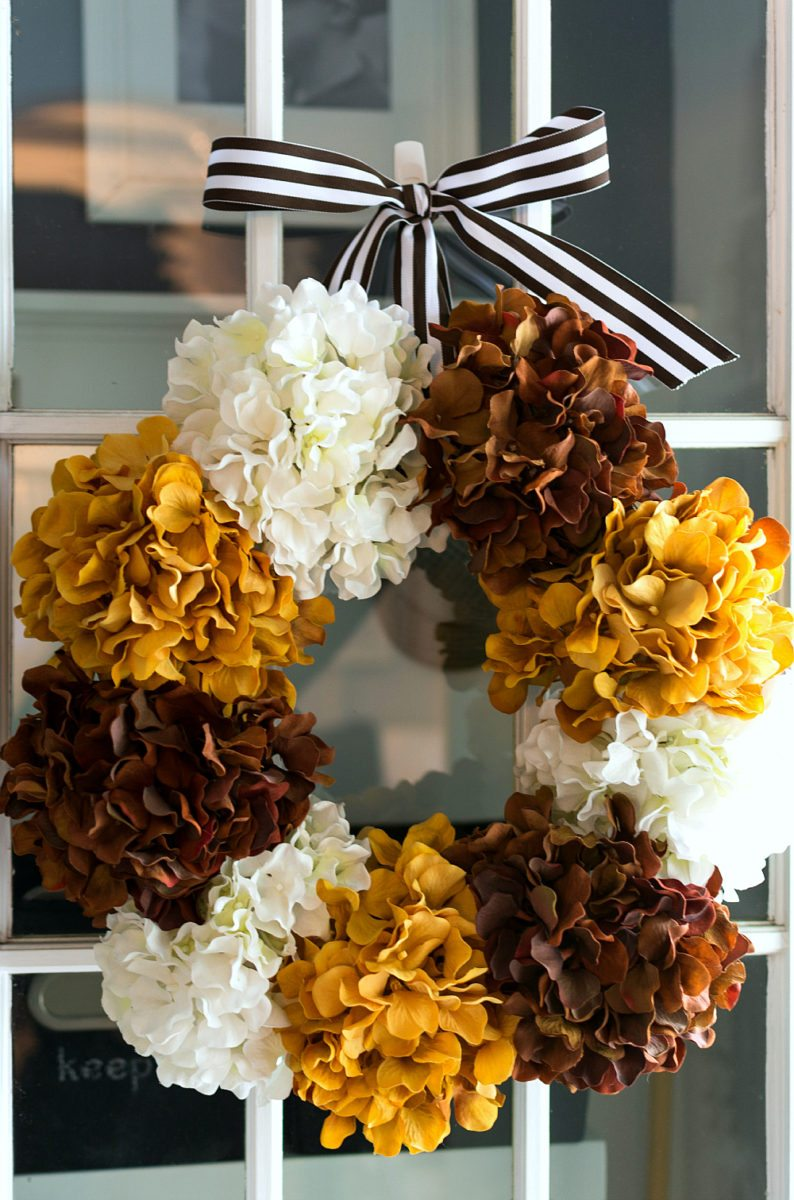 fall wreath ideas hydrangeas of white brown and mustard yellow and hung with a brown and white stripped ribbon on a door.