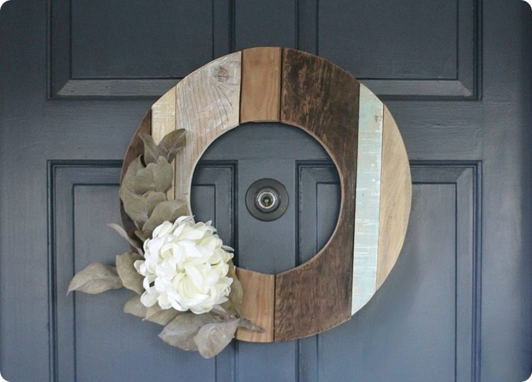 fall wreath made from reclaimed wood.  Cut in the shape of a big circle with an opening in the middle and a large white flower and greenery on the left side.  Wreath created by Lovely Etc.