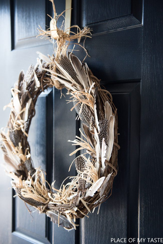 fall wreath ideas made of a grape vine wreath and decorated with raffia and beautiful spotted feathers and gray feathers and hung by raffia or twine on a dark colored black or navy door.