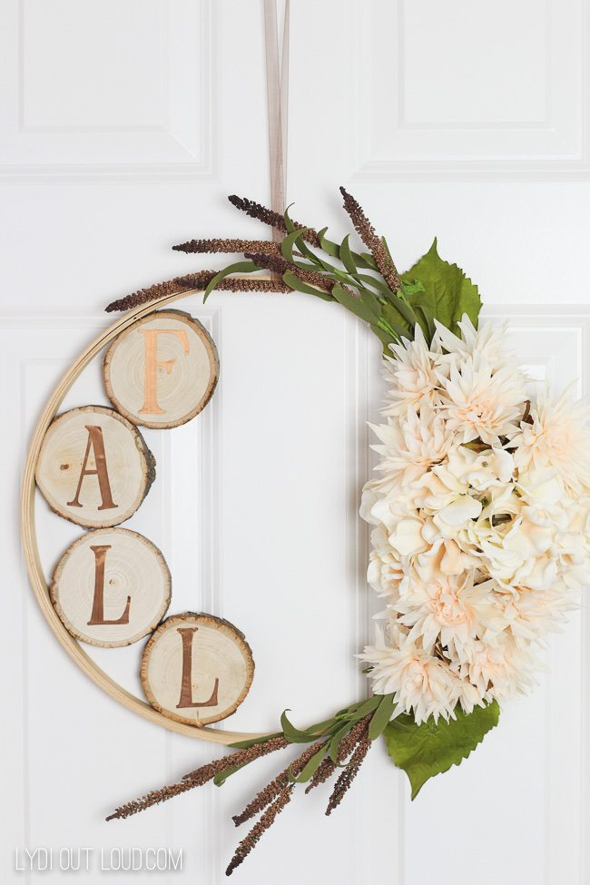 Fall wreaths created on a hoop and on one side are greenery and white flowers and on the inside of the other side is wood slices with gold letters on each wood slice that spells F A L L