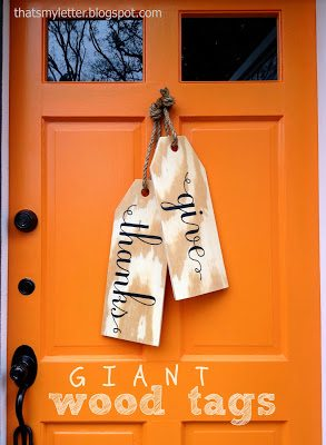 fall wreath ideas give thanks tags.  Large wooden tags hanging on a orange door by knotted ropes.