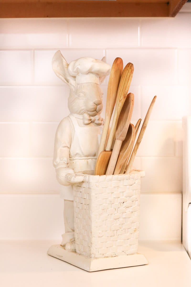 how to organize your kitchen cabinets with the baking and cooking zone.  A bunny holding a basket full of wooden spoon.