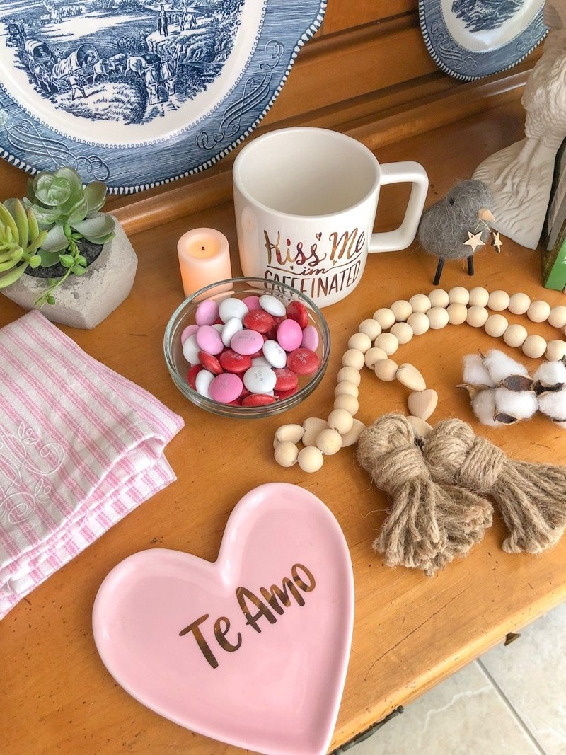 Styling tiered trays with Valentine accessories like a pink and white stripe dish towel, small glass bowl of pink, red and white m&m's, wooden beads, kiss me coffee mug, candle, plant and more.