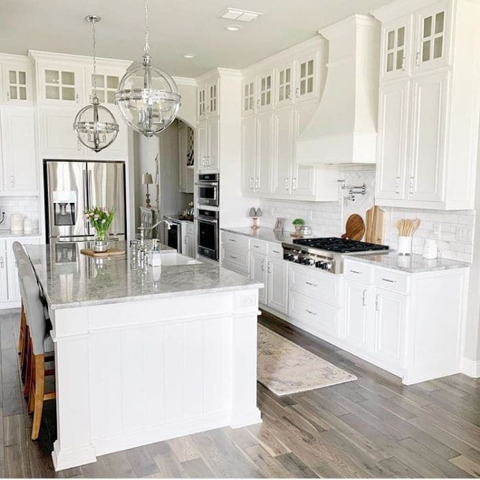 Farmhouse Kitchen by BMA 21 with a white kitchen with gray marble countertops, an oversized kitchen island and white subway tile backsplash