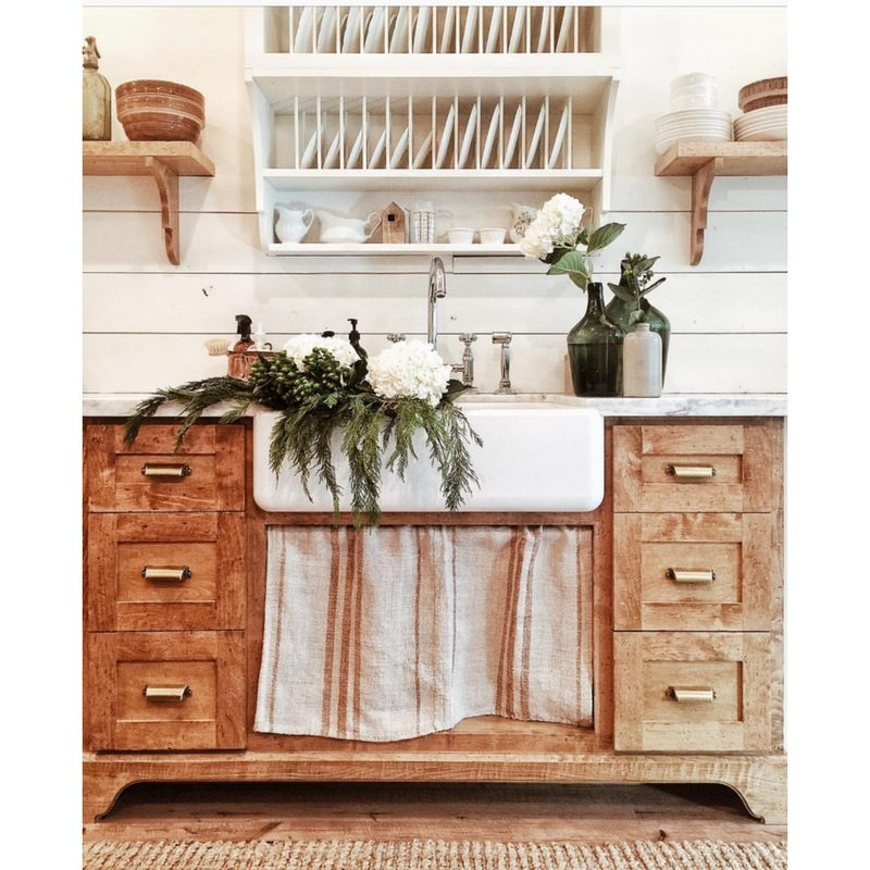 Farmhouse Kitchens by Whitetail Farmhouse with an apron sink and wood cabinetry and flowers in the sink and slatted open shelves with dishes in it above the sink