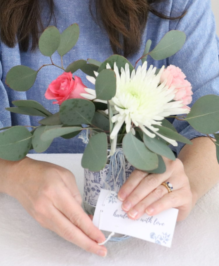 Arranging flowers in a May Day Mother's day toile wrapped upcycled salsa jar and adding a free printable gift tag.