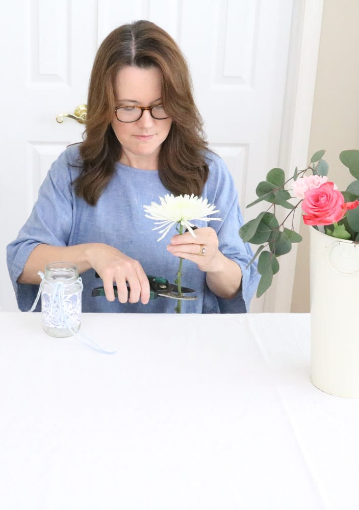 Arranging flowers in a May Day Mother's day toile wrapped upcycled salsa jar.