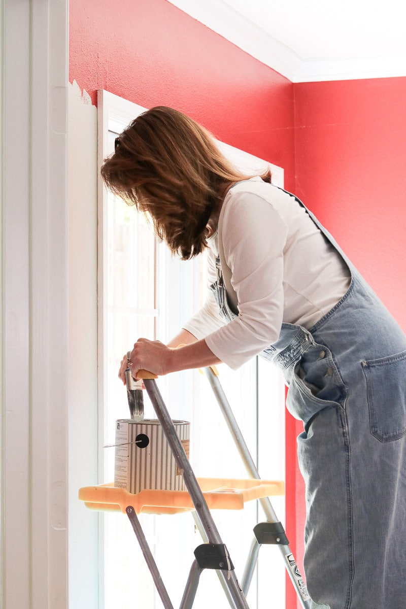 Standing on a ladder to paint a red room gray.