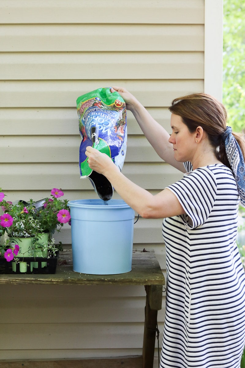 Container flower gardening adding soil to the pot