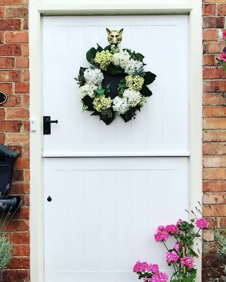 Modern Front Doors by Happy Hound Family with a white from door on a brick home and a white and green hydrangea flower wreath