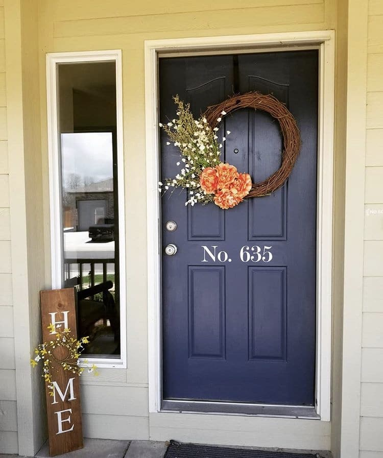 Modern Front Doors by Queen Wood Designs with a navy blue front door with a grapevine wreath and  white vinyl address numbers and a wooden home sign