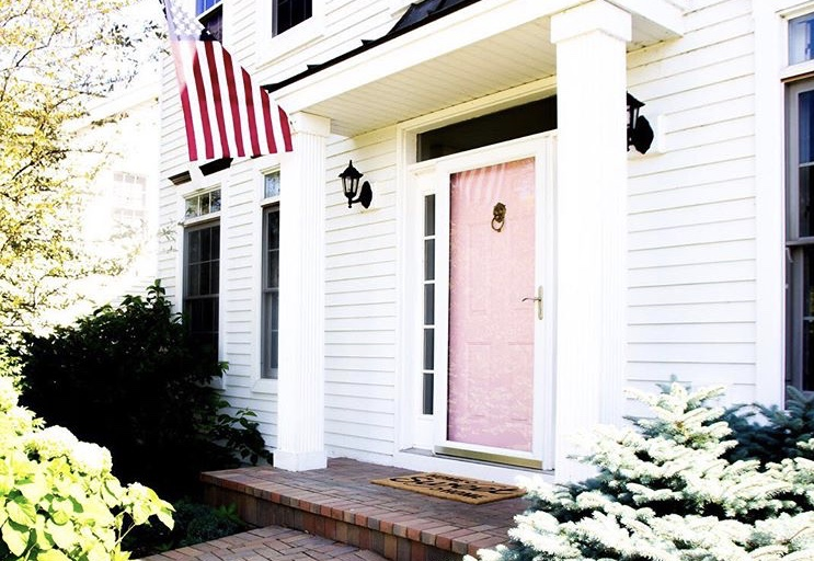 Modern Front Doors byShining On Design with a pink front door on a white home and an American flag hanging from a column