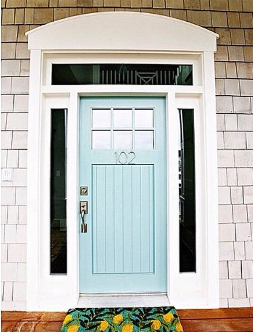 Modern Front Doors by HI Ya Papaya Mom with a light blue door with silver thin metal house numbers and a lemon welcome mat