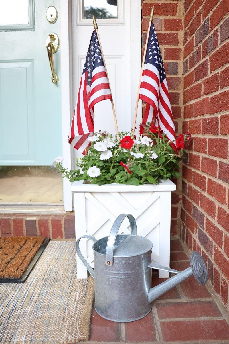 4th of July decorating ideas on a small front porch with red and white petunias in a white planter and flags sticking out of the top