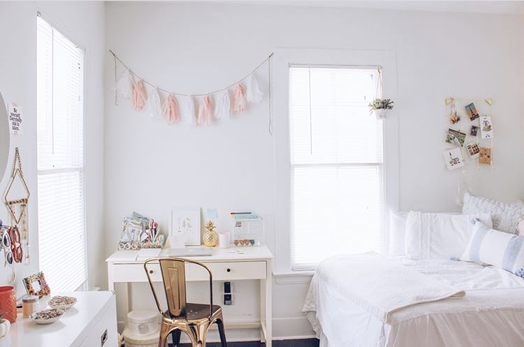 College Dorm Decor Stylin Cafe photograph.  White desk with gold farmhouse style metal chair.  Garland of pink and white paper tassels over desk.  White bedding with white pillows and white throw on bed.