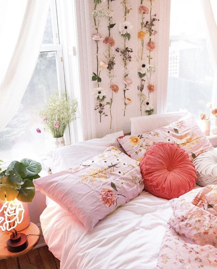 College Dorm Decor Delaney Poli picture.  Flowers hanging on the wall with floral pink bedding, white pulled back curtains and coral round pillow in the middle of the shams.