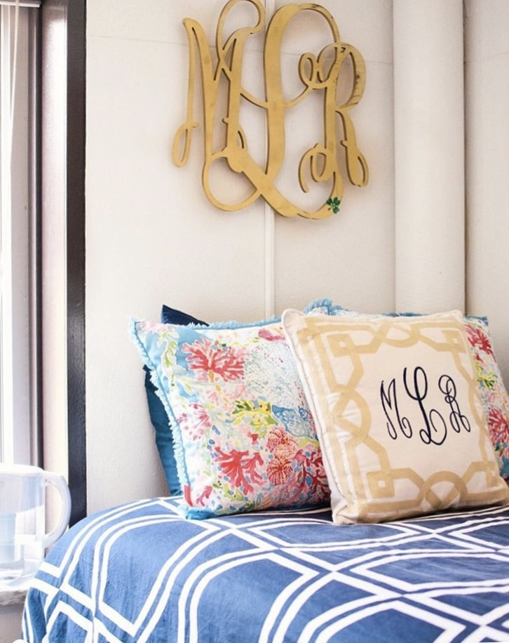 College Dorm Decor Morgan Rose Blog photograph.  Blue and white geometric comforter, Lilly Pulitzer pillow sham, gold and white lattice pattern pillow with monogram.  Gold large monogram on wall above the bed.  Preppy style room.