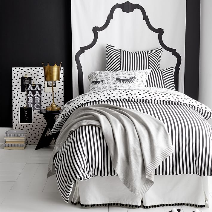 College Dorm Decor Black and White Pottery Barn photograph.  Black and white strip comforter with polka dot on other side and shams with white bed skirt that has black tassels on the bottom. Light grey throw on foot of the bed and another gray and white pillow sham with eye lashes.  Black night stand with gold crown lamp.