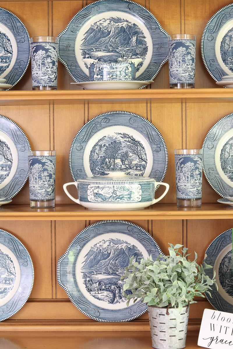 Currier & Ives dishes in a farmhouse hutch