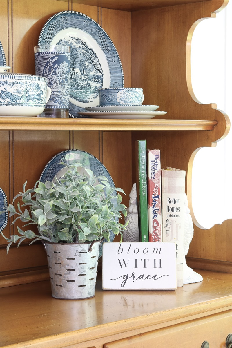 Accessories with iron rooster bookends, old and new cookbooks, plant and bloom with grace plaque for a farmhouse hutch