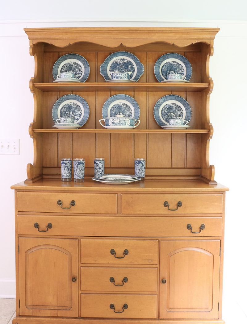 Layer smaller plates, cup and saucers on the sides in this farmhouse hutch
