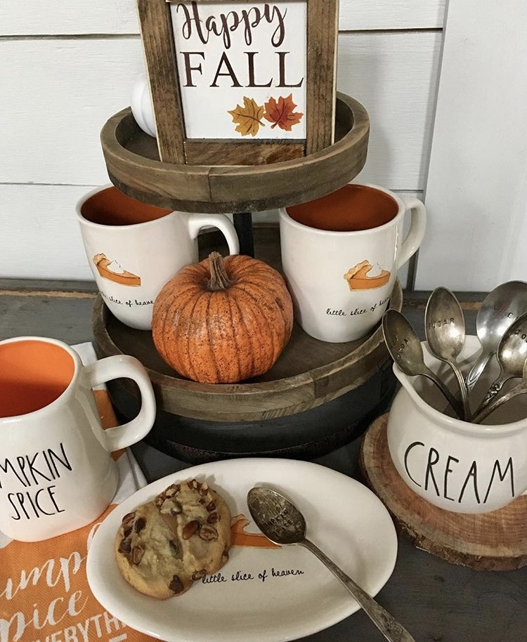 Fall Decor wooden tiered tray coffee station by Grams Farmhouse. This autumn filled tray has two tiers and delicious coffee cups with pumpkin pie on them and an rustic orange pumpkin. With loads of Rae Dunn and topped with a Happy Fall sign.