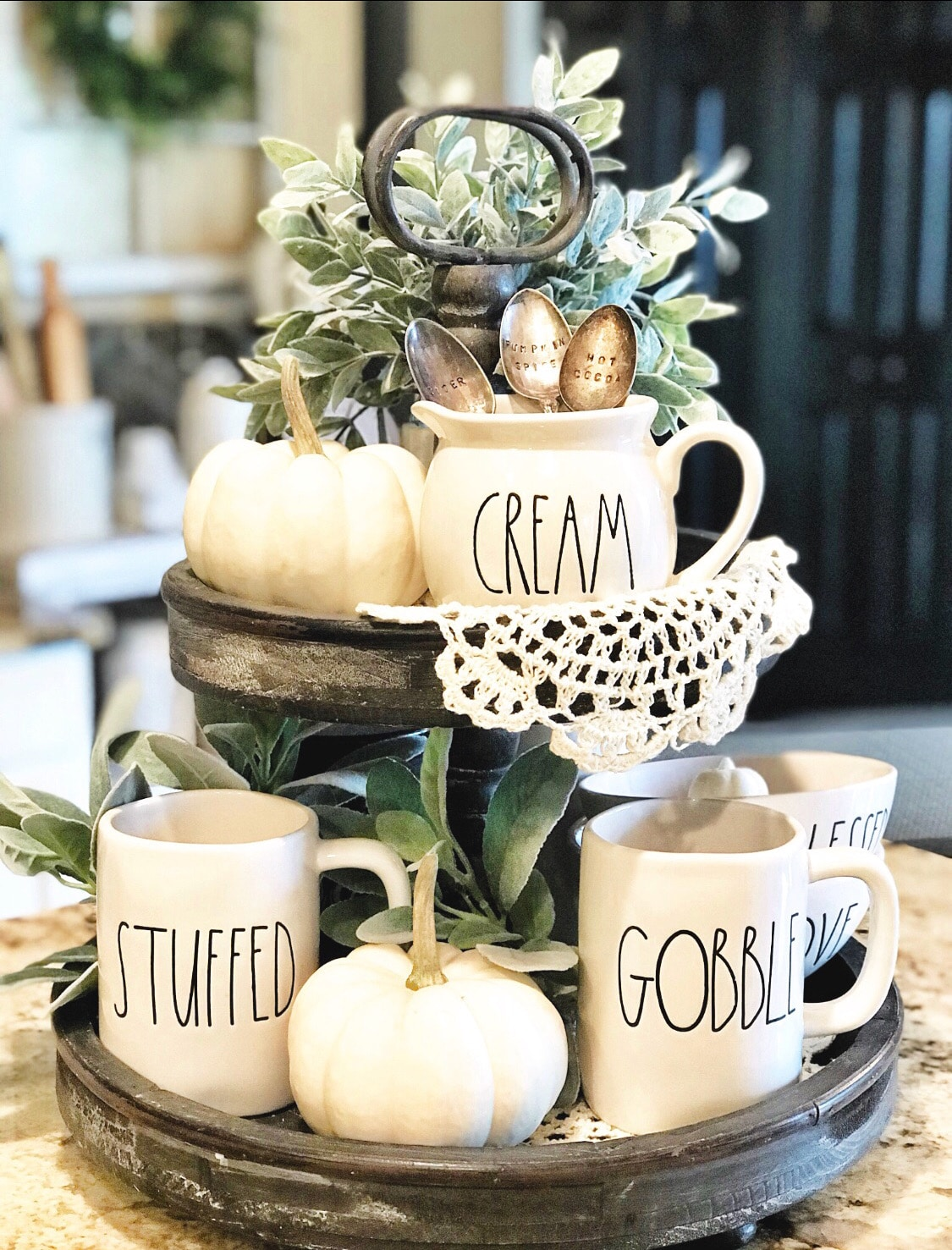 Fall Decor rustic two tiered tray by Farm to Table Creations. This tray idea is packed with rae dunn goodness, plants, white pumpkins and delicate lace. This tray can stay out for Halloween, all autumn and Thanksgiving.