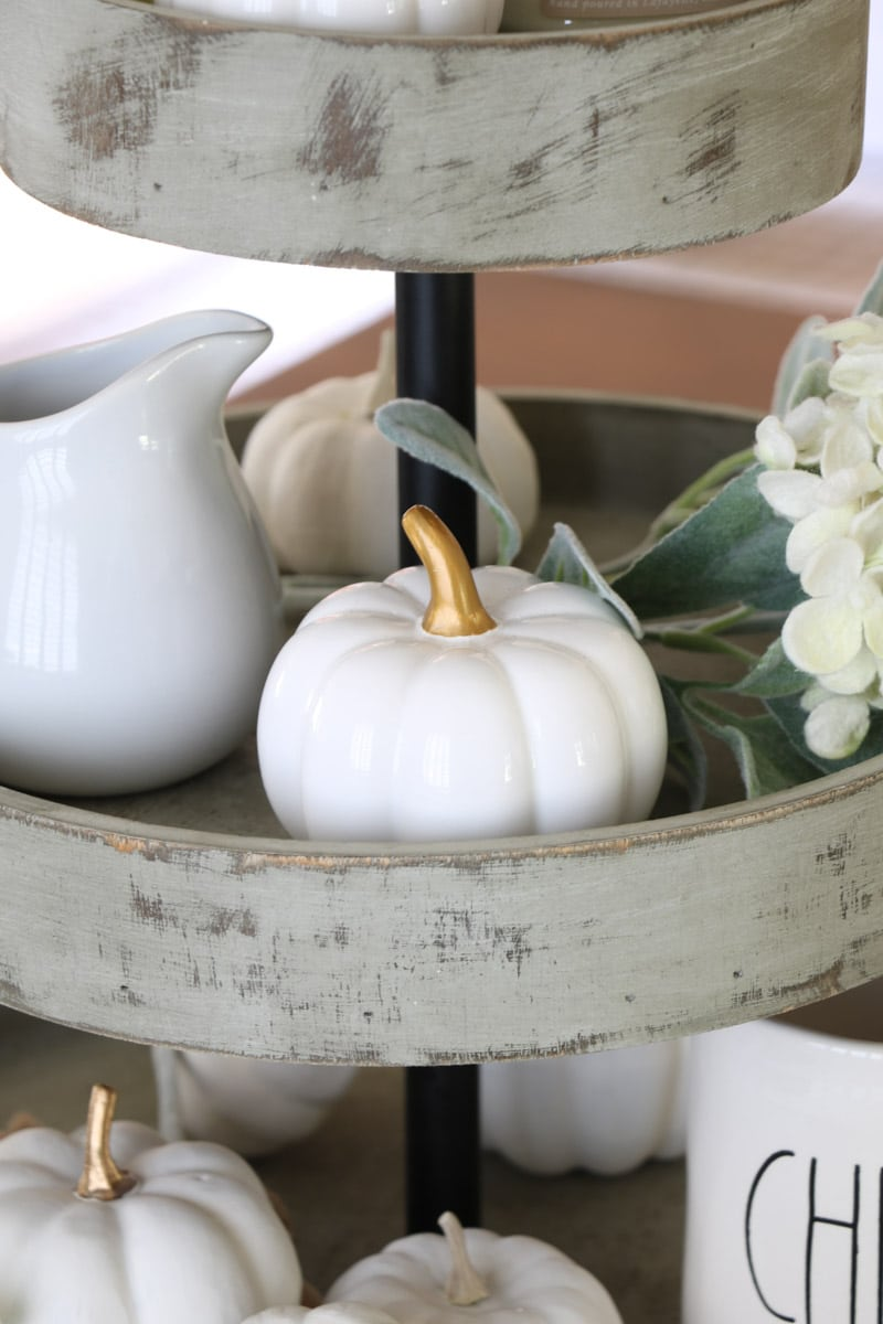 3 tiered wooden stand filled with harvest decorations like white creamer and pumpkin as a centerpiece on a dining table