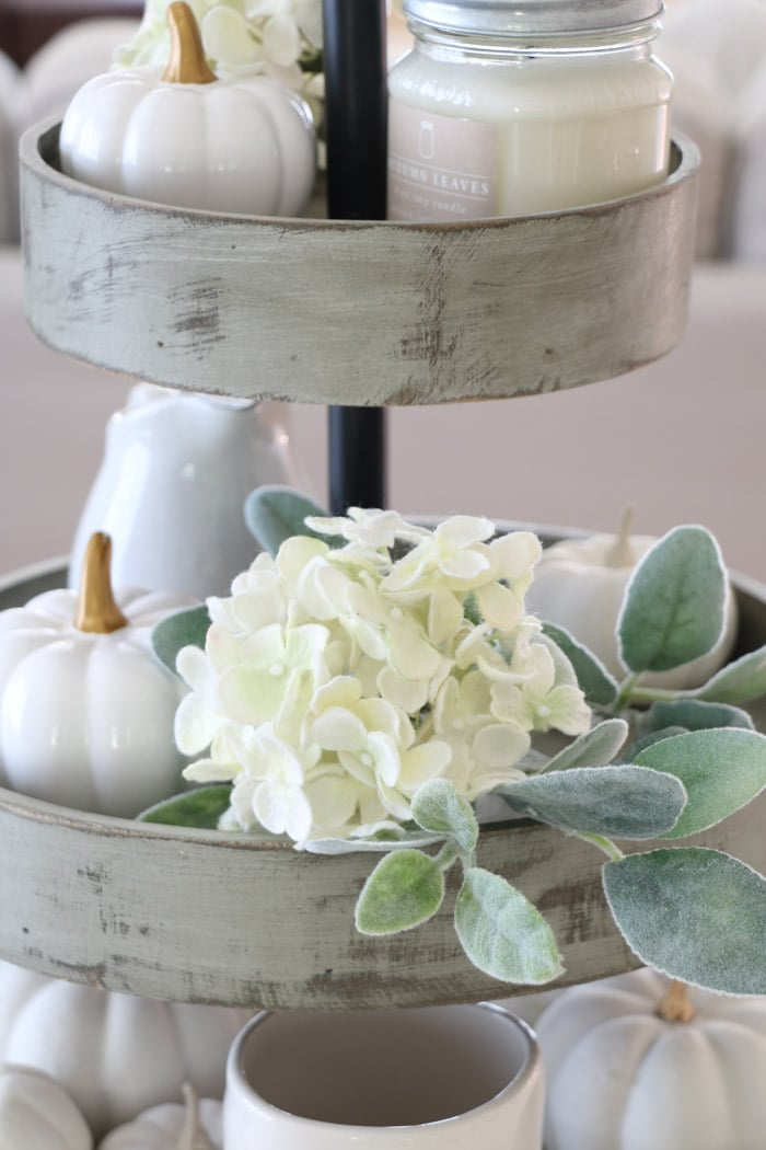 3 tiered wooden stand filled with harvest decorations like white hydrangea, lambs ear and pumpkin as a centerpiece on a dining table