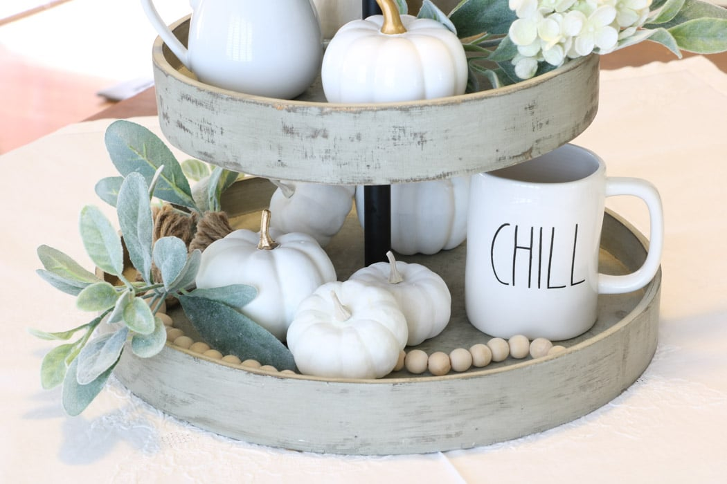 3 tiered wooden stand filled with harvest decorations like white pumpkins, wood bead garland as a centerpiece on a dining table