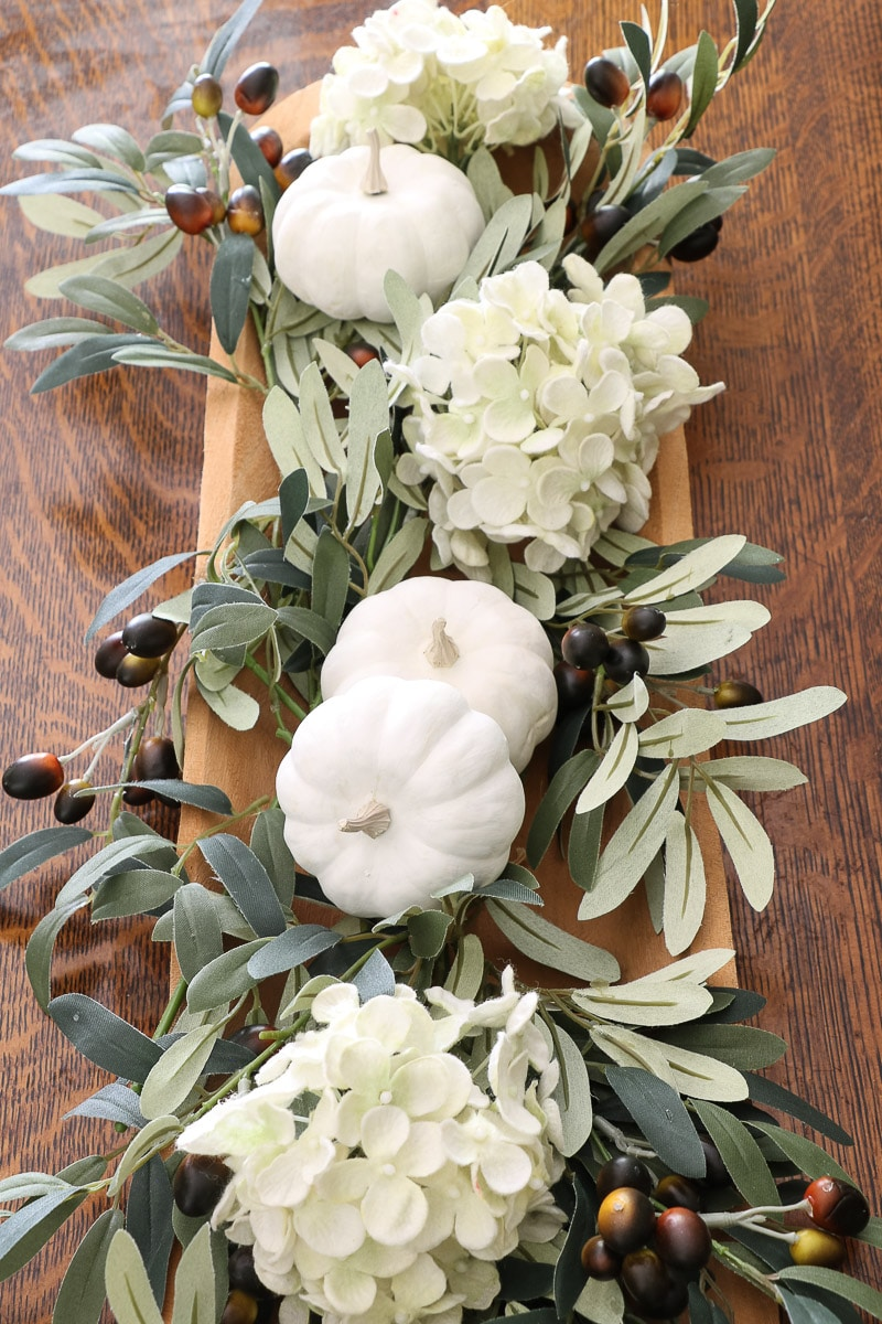 fall floral arrangement using olive branches, white hydrangeas and white pumpkins