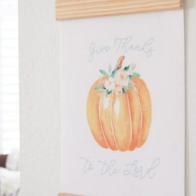 Fall Free Printable of a pumpkin with flowers and bible scripture from Psalms 107:1 Give Thanks to the Lord