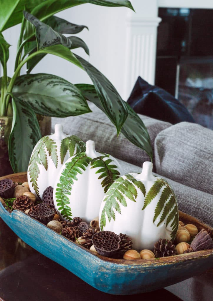 Decorating with dough bowls by Deeply Southern Home. This hand painted down bowl is filled with white painted pumpkins and fern leaves