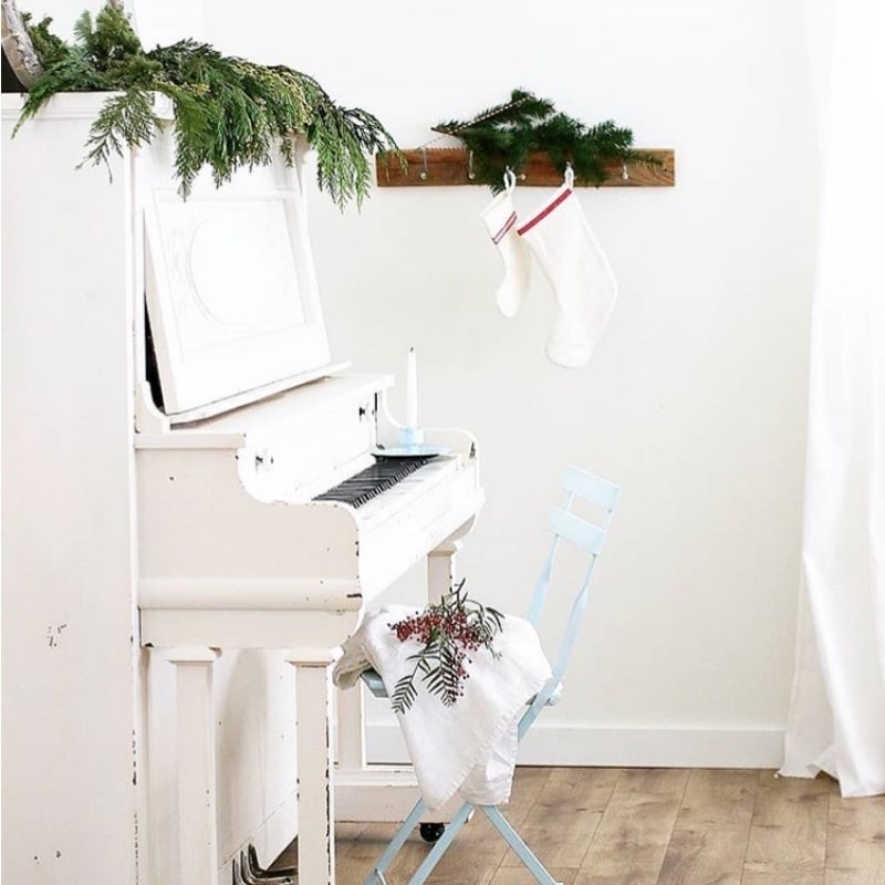 Minimalist Christmas Decorations by Hollie Keller greenery on a piano, holly and stockings hung