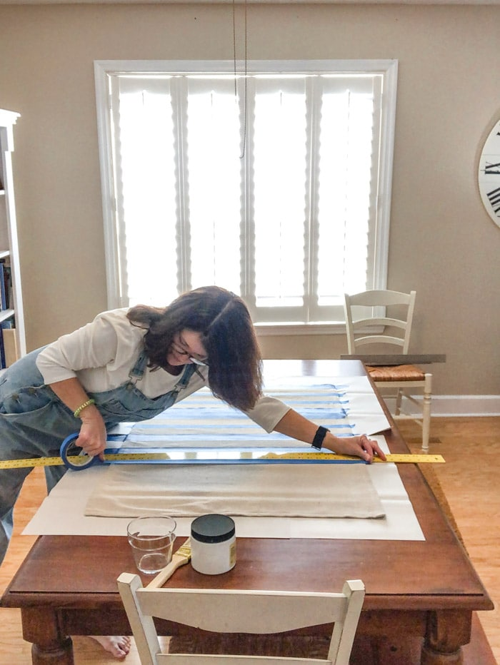 DIY rug using a drop cloth and chalk paint and painters tape to paint stripes