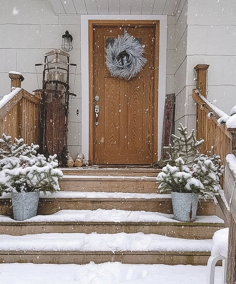 Christmas decorating ideas for porches by Devon Lee Carroll snow falling, trees in metal buckets, white twig wreath and sleds