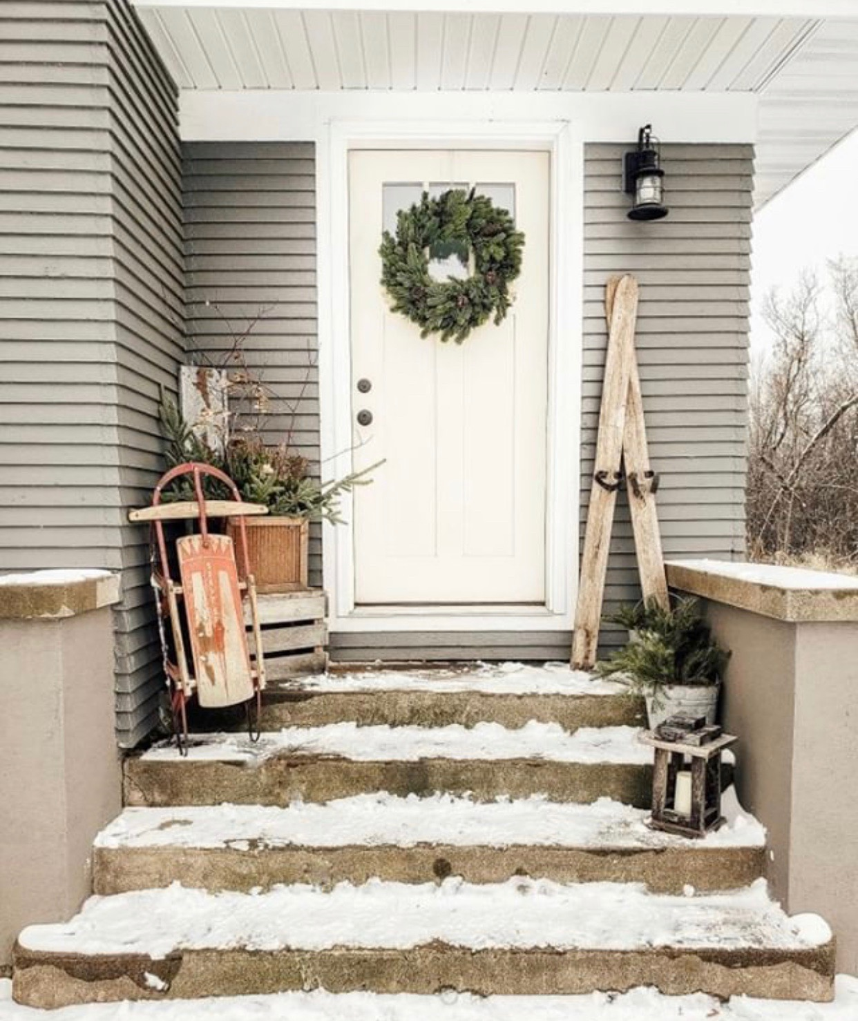 Christmas decorating ideas for porches by Farmhouse for 8 with a sled, skies and greenery and a lantern