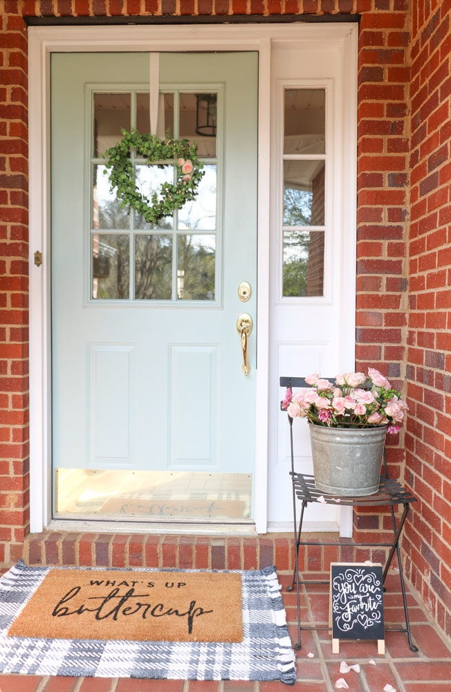 Valentine's Day porch decor ideas with roses in an antique galvanized bucket, signs and layered carpets.