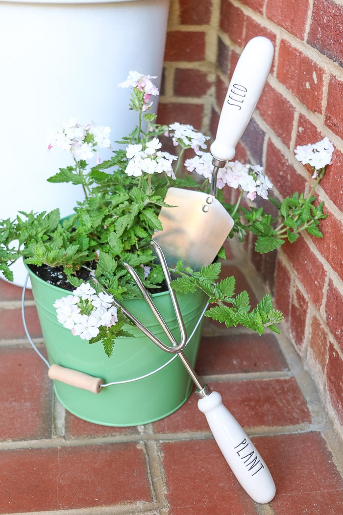 spring porch decorating ideas with potted plant in metal bucket and Rae Dunn gardening tools