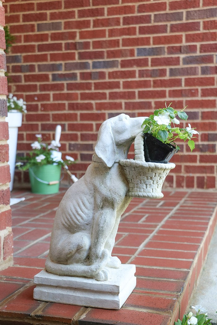 spring porch decorating ideas with dog statue holding a basket of flowers