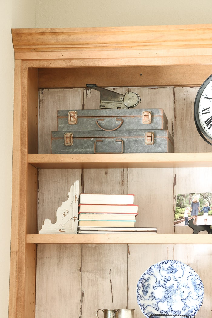 how to decorate a bookcase by adding old vintage boxes
