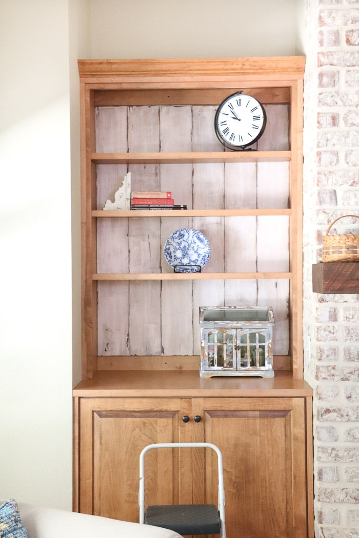 how to decorate a bookcase by adding larger items on each shelf