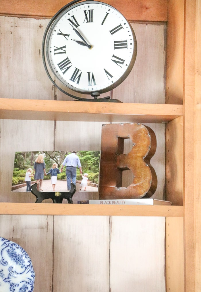 how to decorate a bookcase by adding medium size items on the shelves