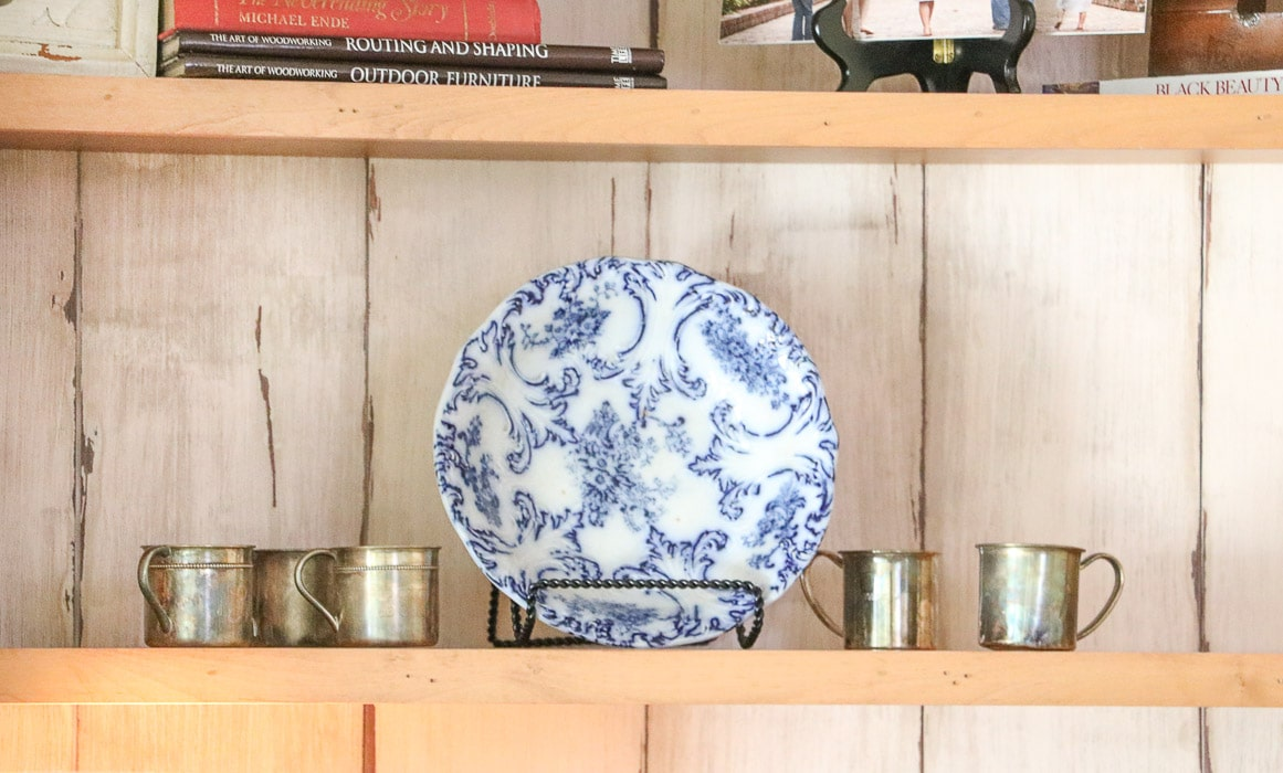 how to decorate a bookcase by adding a plate in the middle of a shelf
