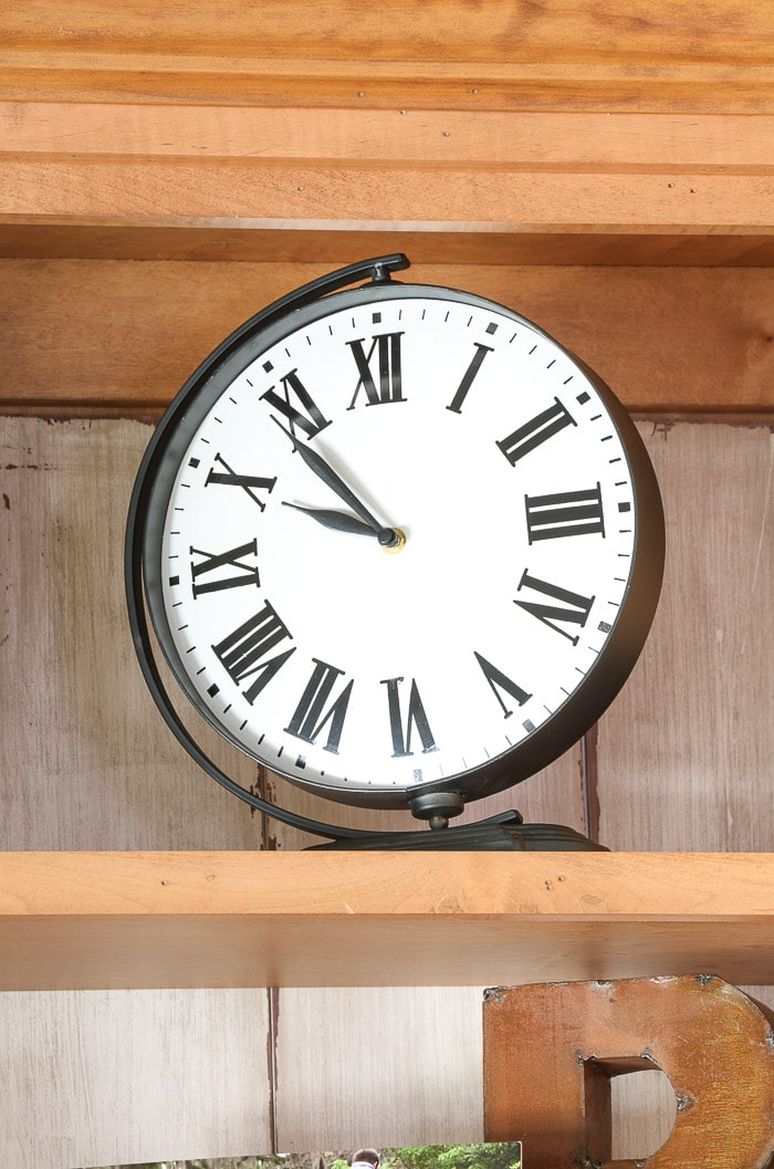 how to decorate a bookcase by adding a large clock to the top shelf